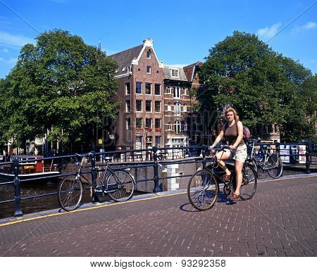 Cyclist on canal bridge, Amsterdam.