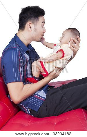 Happy Father Playing With Baby On Sofa