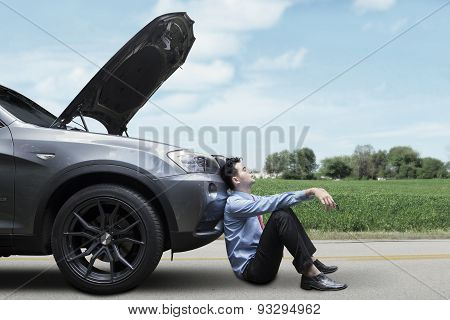 Man Sitting On The Road With Broken Car
