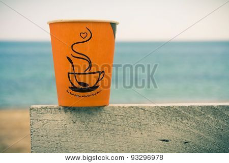 Orange Disposable Cup Of Coffee Standing On A Wooden Fence