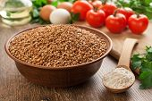 picture of ceramic bowl  - Composition with ceramic bowl dry buckwheat eggs tomatoes and parsley in the background - JPG