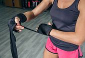picture of boxing  - Closeup of beautiful woman wrapping his hands with protective bandages before boxing training in the gym - JPG