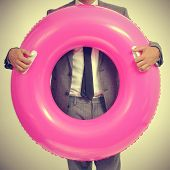 stock photo of floaties  - a young caucasian businessman wearing a grey suit with a pink swim ring - JPG