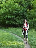 stock photo of sling bag  - Young mother walking in the Park and holding a small child in a Baby Carrier bag - JPG