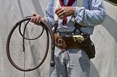 stock photo of whip-hand  - A cowboy stands in front of a canvas tent with a bull whip in hand a revolver in his holster - JPG