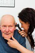 stock photo of eardrum  - Doctor examining elderly patient - JPG
