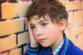 image of preteen  - preteen handsome boy close up outdoor portrait on the yellow brick wall background - JPG