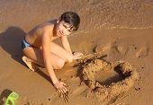 stock photo of preteen  - preteen handsome boy sculpturing sand heart on the red sea beach - JPG