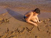 image of sun-tanned  - preteen handsome sun tanned boy on the red sea beach whrite love on the sand - JPG