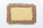 image of millet  - Classical frame made of burlap with grains of millet on a white background - JPG