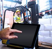 stock photo of forklift  - Man using tablet pc against focused driver operating forklift machine - JPG
