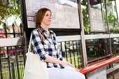 image of bus-shelter  - a young woman waiting for the bus - JPG
