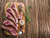 stock photo of lamb chops  - Raw lamb chops with garlic and herbs on the old wooden table - JPG