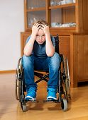 picture of sad boy  - disabled boy in wheelchair at home is sad - JPG