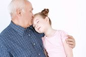 image of she-male  - Portrait of a grandfather wearing blue checkered shirt hugging his small pretty granddaughter and kissing her forehead while she is closing eyes  - JPG