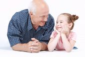 stock photo of granddaughters  - Portrait of a grandfather wearing blue checkered shirt and his small pretty granddaughter lying near looking at each other and smiling - JPG