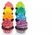 stock photo of icing  - Chocolate cupcakes in rows with colorful icing on a white background - JPG