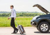 pic of leaving  - Full length side view of young businessman with suitcase leaving broken car at countryside - JPG