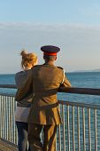 image of track home  - A girl in a track suit and a guy in his army suit turning away from the camera looking at the sea while standing at the pier at sunset hour on a summer day with no clouds in the sky - JPG