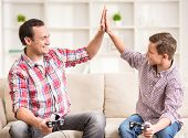 picture of indoor games  - Father and son dressed casual having fun at home while playing computer games - JPG