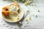 picture of chamomile  - Glass of chamomile tea with chamomile flowers and tasty muffins on color wooden background - JPG