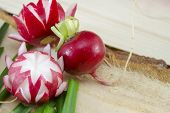 foto of radish  - Decorated red radish on a rough wooden surface