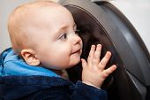 picture of fascinating  - Portrait of a cute little baby boy looking with fascination inside the washing machine  - JPG