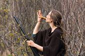 picture of hunter  - Woman hunter with wooden duck call in spring forest - JPG