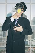 picture of rubber mask  - Male entrepreneur standing in the office with gas mask and getting heart attack - JPG