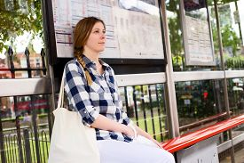 picture of bus-shelter  - a young woman waiting for the bus - JPG