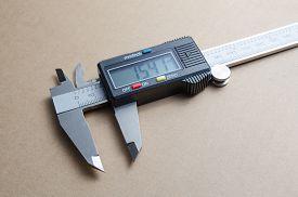 picture of vernier-caliper  - Digital electronic vernier caliper on a brown background - JPG