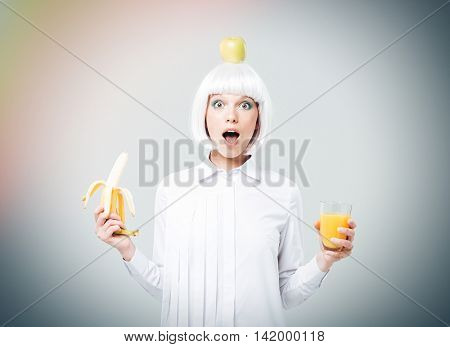 Wondered young woman with apple on her head holding banana and glass of juice over white background