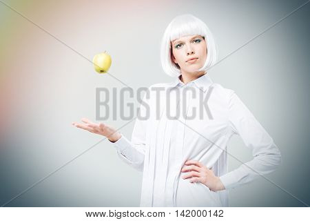 Beautiful young woman in blonde wig standing and throwing apple in the air over white background
