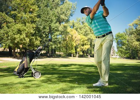 Golfer preparing to play from fairway, toned image