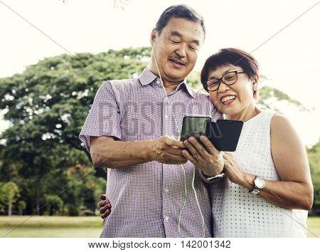 Senior Couple Cheerful Earphones Mobile Concept
