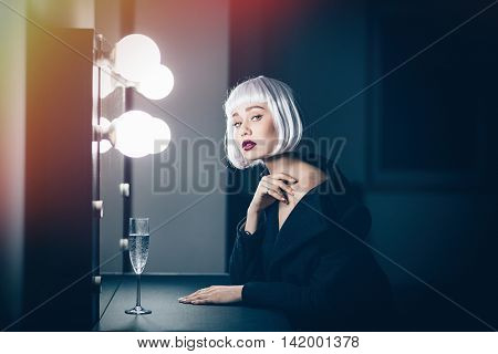 Gorgeous blonde young woman in black coat sitting in dressing room