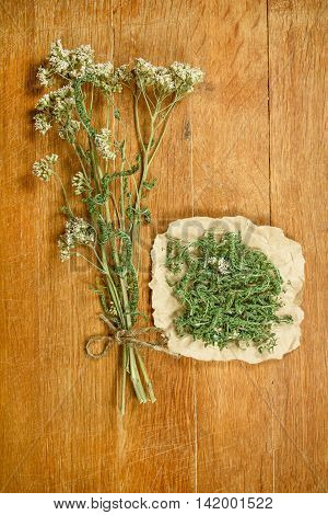 Yarrow.Dried herbs for use in alternative medicine.Herbal medicine phytotherapy medicinal herbs.For preparation of infusions decoctions tinctures powders ointments tea.Background wooden board