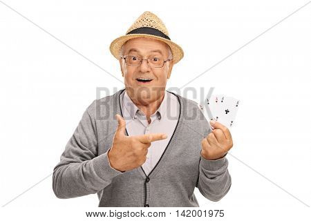 Senior man holding four aces in one hand and pointing at them with his other isolated on white background