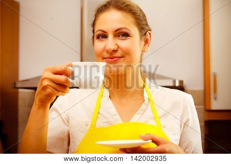 Mature Woman Drinking Cup Of Coffee In Kitchen.