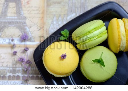 Lemon and mint flavor french macarons on black plate