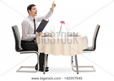 Young man calling the waiter and sitting at a restaurant table isolated on white background