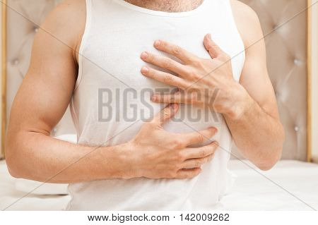 Man In White Shirt With Hands On Chest