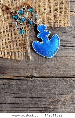 Anchor charm keychain for beach bag or car. Blue felt ornament with beads on old wooden background. Crafts idea for children, women, beginners. Simple summer diy. Top view