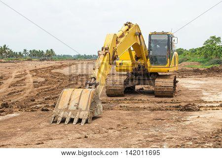 Yellow excavator at quarry site in Thailand.
