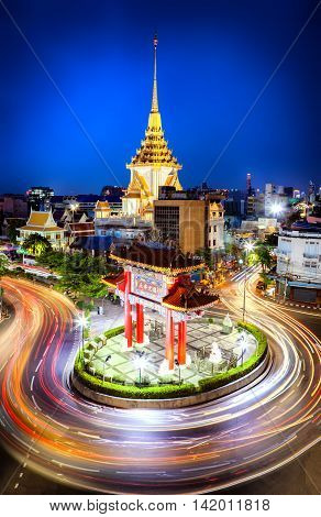 The gateway arch (Odeon Circle) and Traimit temple behind with light trails from long exposure photo taken Landmark of Chinatown Bangkok Thailand. (Chinese character is meant