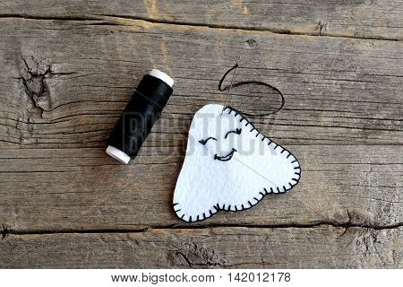 How to make handmade Halloween ghost ornament. The two white felt pieces sewn black thread. Step. Crafts instruction for children. Closeup. Top view