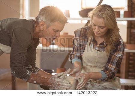 Male potter assisting female potter in pottery workshop