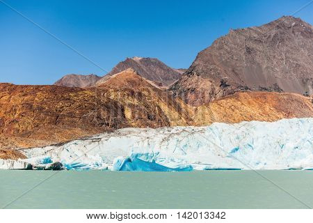 Unique lake Viedma in Patagonia. The enormous glacier sliding into the lake. From the edge of the glacier break off huge blue floes. Pleasure tourist boat floats to the glacier
