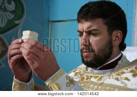 LUTSK UKRAINE - 08 JANUARY 2009: Priest consecrates bread during orthodox liturgy ceremony.
