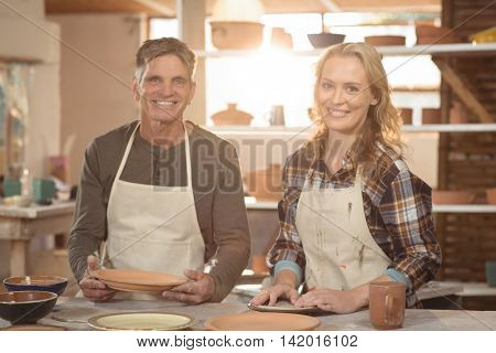 Portrait of smiling potters working together in pottery workshop